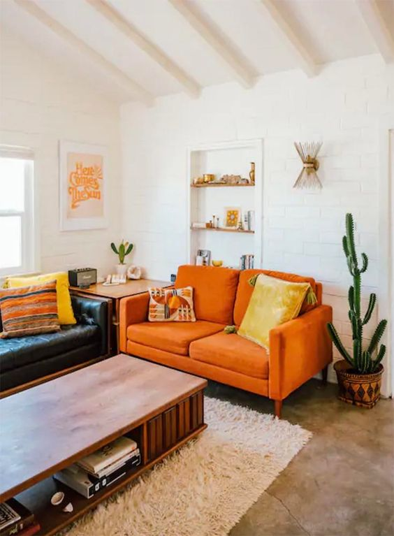 a boho living room with a black leather sofa, an orange loveseat, a low table and potted cacti feels warm and cool