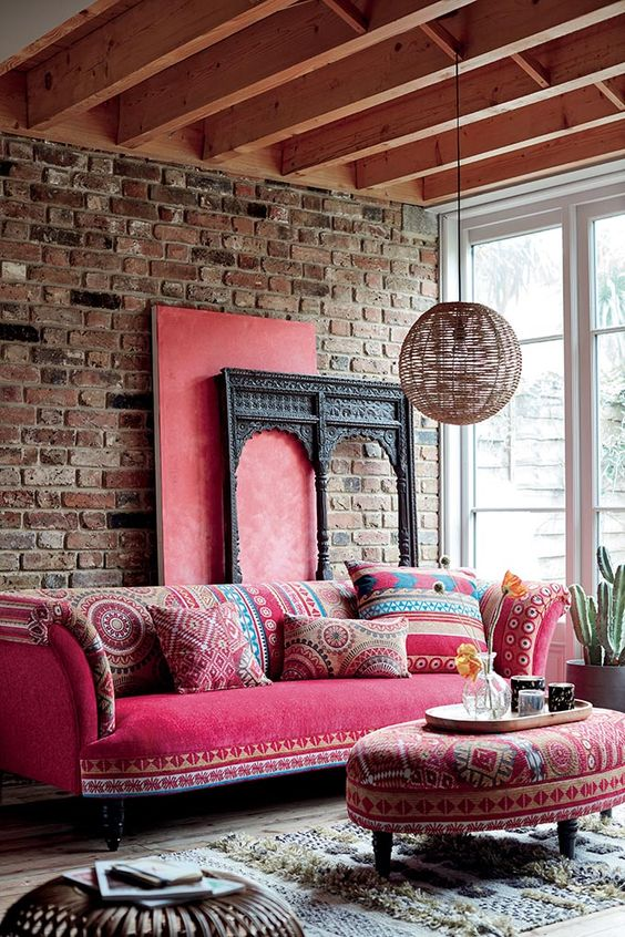 a boho living room with a brick wall, a pink sofa with printed pillows, a matching ottoman, a rattan pendant lamp and a Moroccan rug