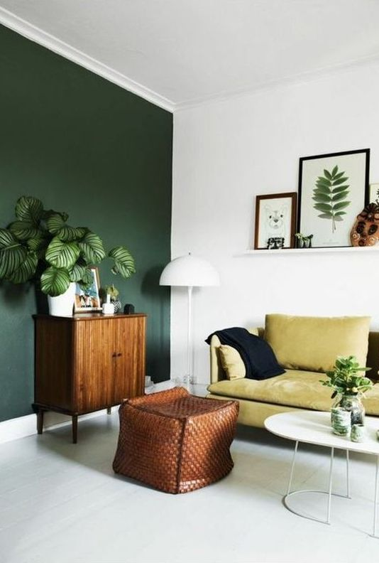 a boho living room with a dark green wall, a yellow sofa, potted plants and a gallery wall on a ledge