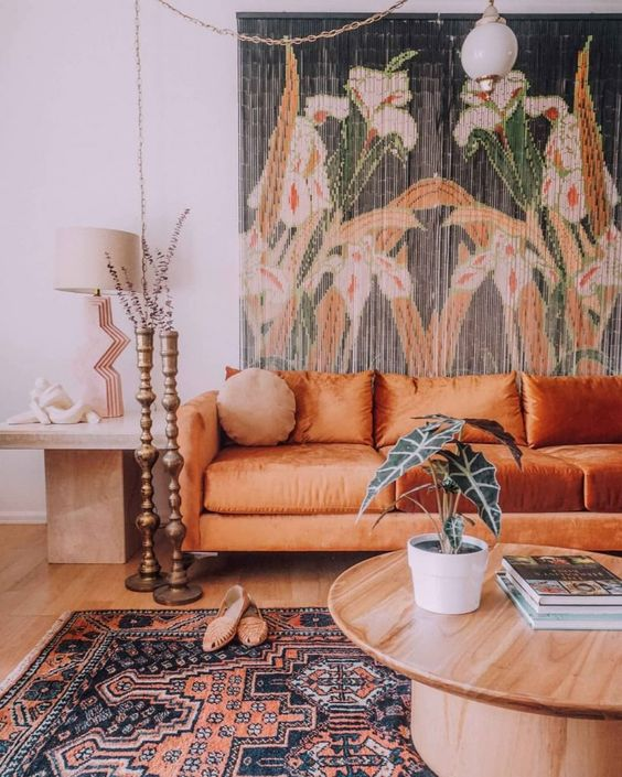 a boho living room with a floral tapestry, an orange sofa, a round table and a side table plus candle holders and a boho rug