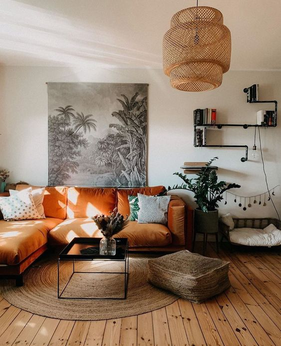 a boho living room with an orange sectional, a low table, a jute ottoman and a rug, a woven pendant lamp and potted plants