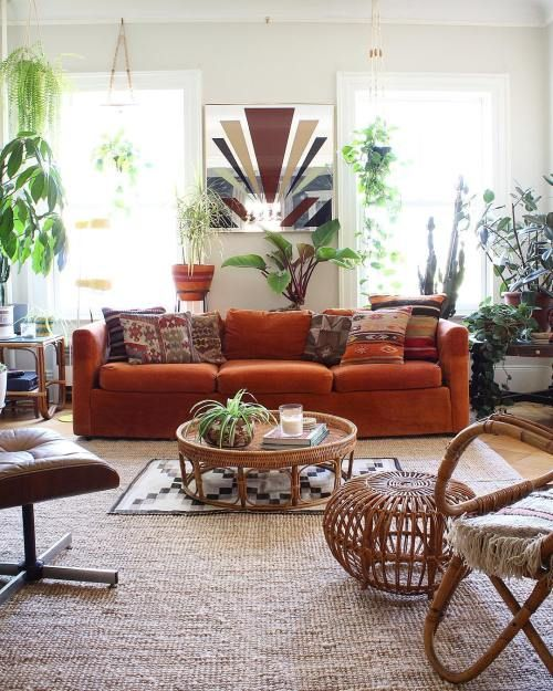 a boho living room with an orange velvet sofa as a centerpiece, potted plants and rattan and leather furniture, boho rugs