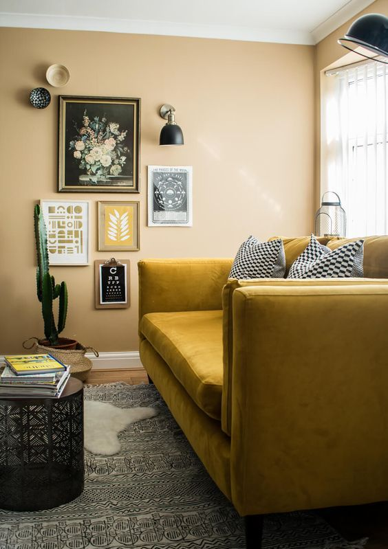 a boho nook with yellow walls, a mustard sofa, a gallery wlal and sconces and layered rugs plus a potted cactus