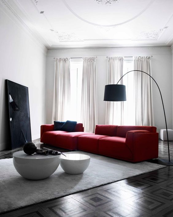 a bold contemporary living room with a large red sofa, a black artwork and a floor lamp and a duo of round tables