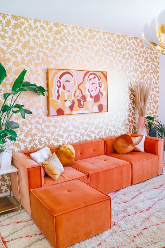 a bold living room with a botanical print wall, an orange sectional, a bold artwork and some plants and blooms