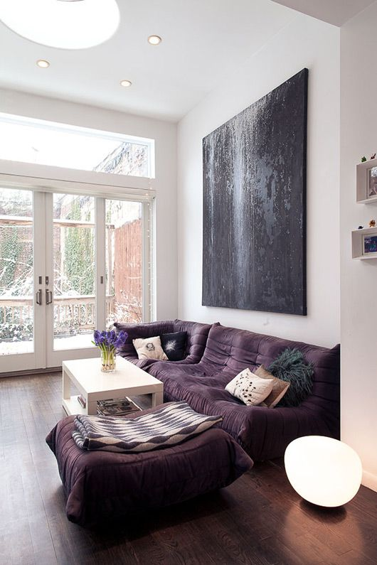 a bold modern living room with a low purple sofa and a large pouf, a white table and an oversized black artwork