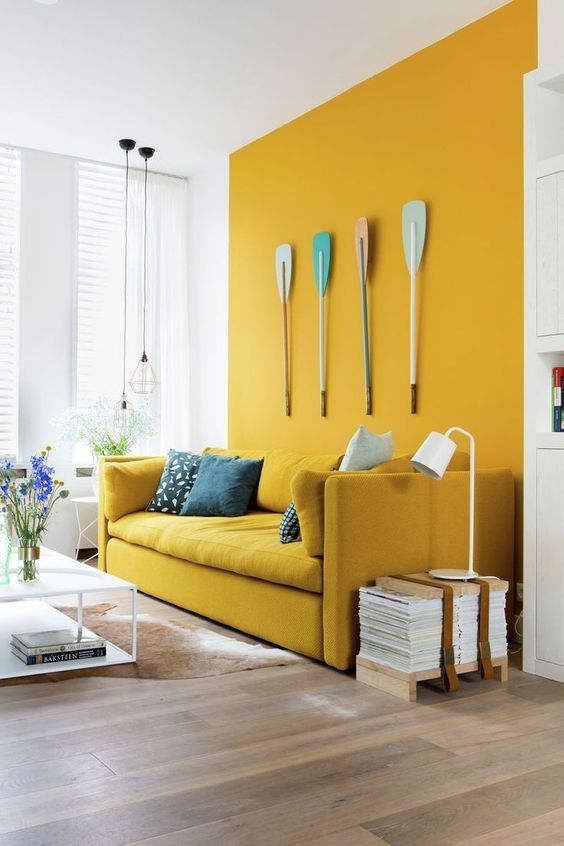 a bold space with a mustard wall and a matching sofa, oars for decor, a low table and stacked magazines is quirky