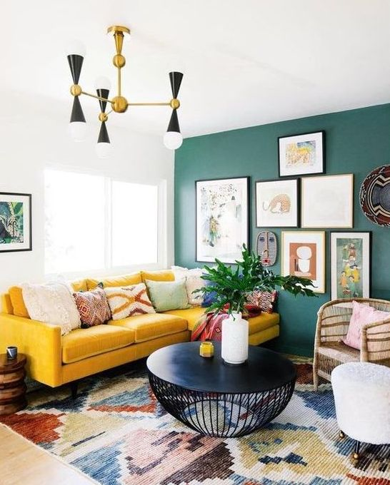 a bright boho living room with a green wall and a gallery wall, a yellow sectional, a retro chandelier and a black round table