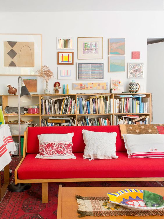 a bright eclectic living room with a bold red sofa, bookshelves, a bright gallery wall and a low coffee table