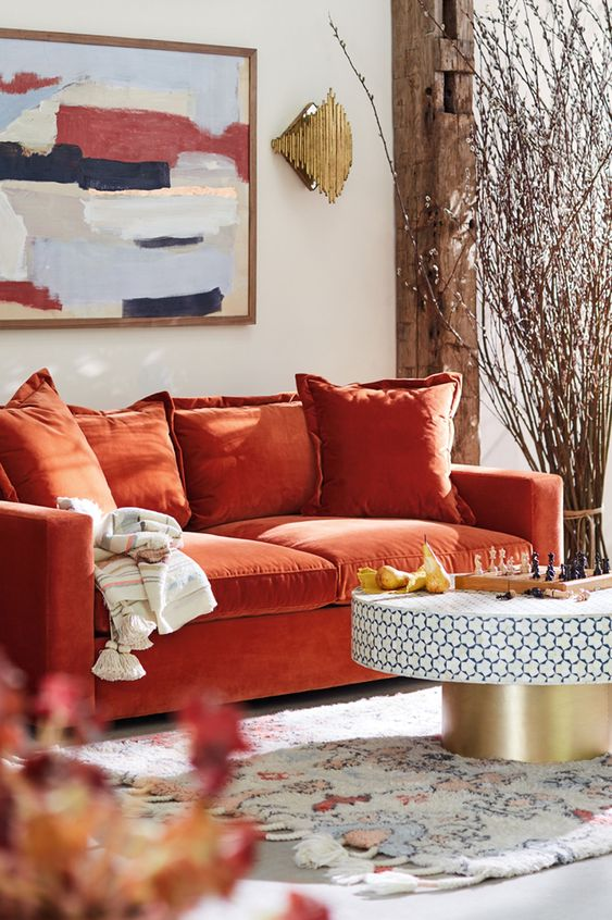 a bright living room with an orange sofa, a round table, a bold artwork and blooming branches arranged for decor