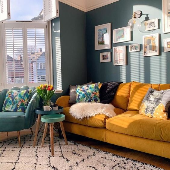 a bright living room with blue walls, a yellow sofa and printed pillows, a blue chair and round tables is chic and welcoming