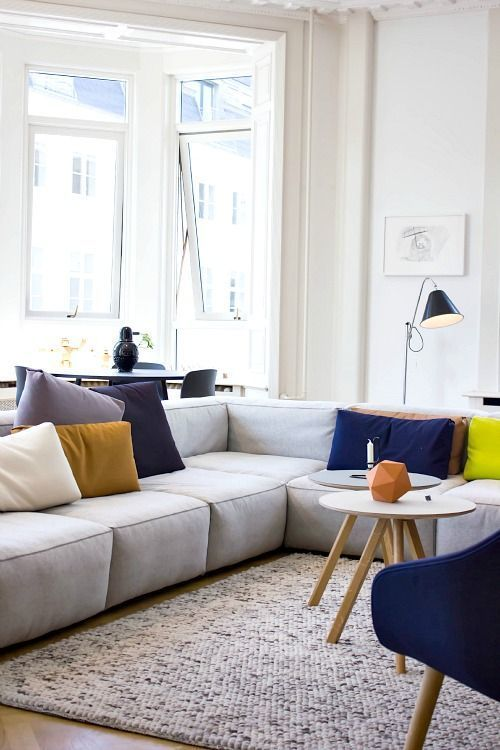 a bright modern living room with a grey low sofa, a bold blue chair, colorful pillows, some lamps and round tables