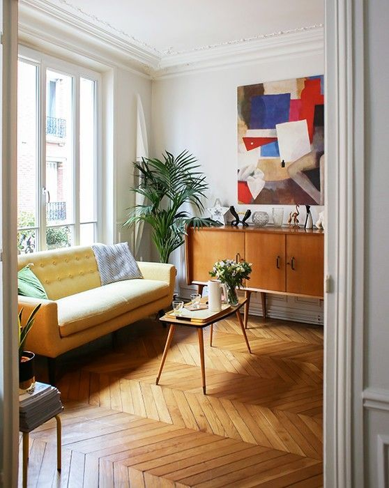a bright modern living room with a light yellow sofa, a colorful artwork, mid century modern furniture and greenery