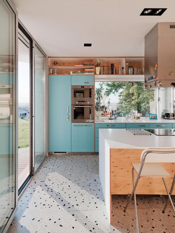a bright turquoise kitchen with a white kitchen island and a grey terrazzo floor is a playful and cheerful and looks bold