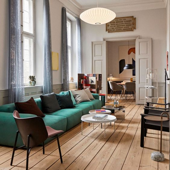 a catchy living room with a low emerald sofa, roudn tables, various chairs, lamps and artworks is chic