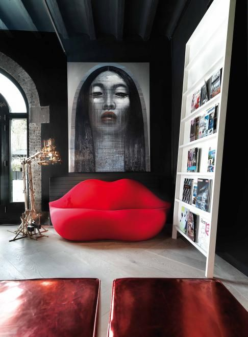 a catchy living room with dark walls, a creative ledge storage unit and ared lip-shaped sofa and a bold artwork