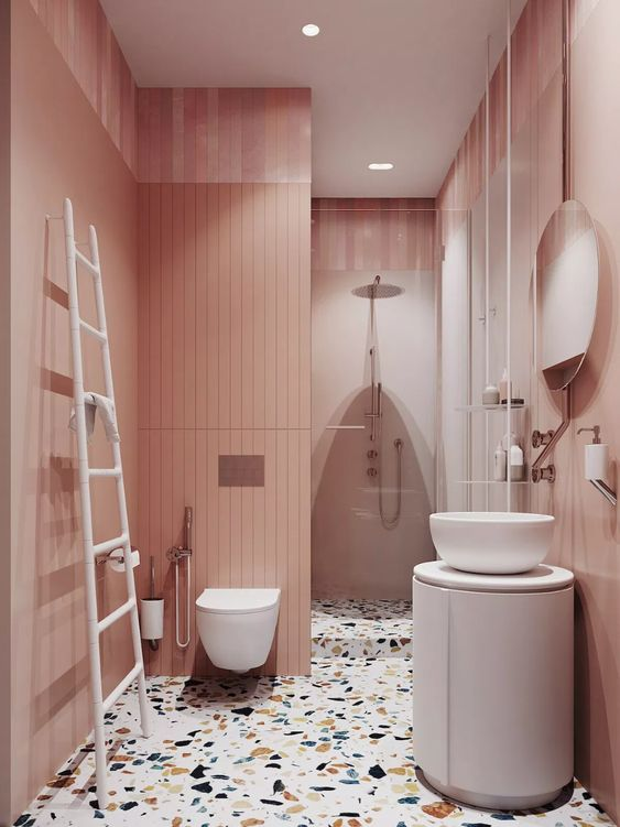 a catchy rose bathroom with pink walls, a colroful terrazzo floor, a roudn vanity and a round sink and a ladder