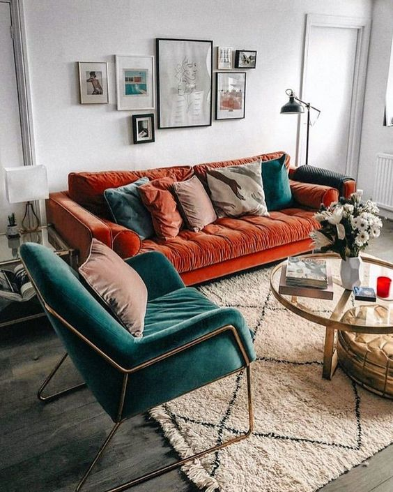 a charming living room with a bold burnt orange sofa, a teal chair and matching pillows plus a lovely gallery wall