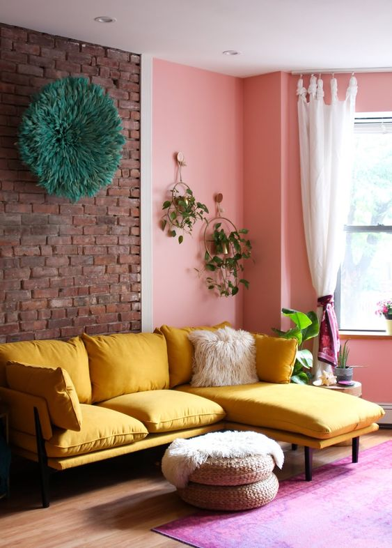 a cheerful living room with a brick and pink wall, a yellow sectional, jute ottomans and greenery is amazing
