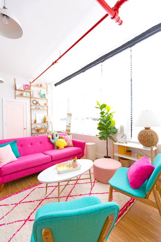 a cheerful living room with a hot pink sofa, turquoise chairs with quirky pillows, a printed rug, a potted plant and a blush pouf