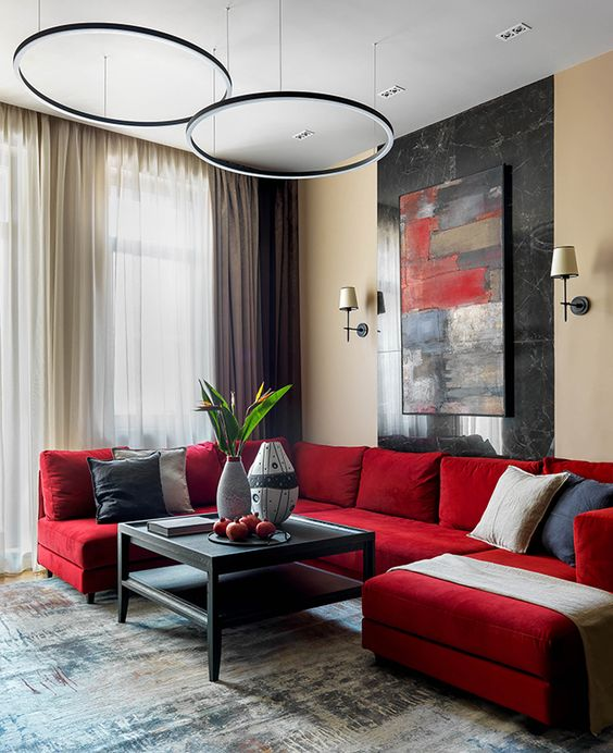 a chic contemporary living room with a red sectional, a bold artwork, pendant lamps, a black low table and various pillows