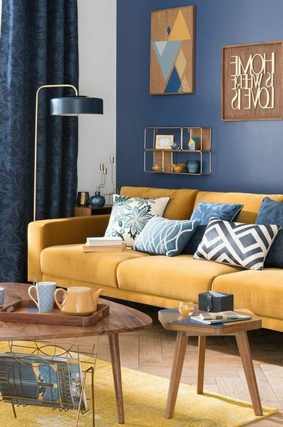 a chic living room with a navy accent wall, a yellow sofa with blue pillows, a yellow rug, a floor lamp and wooden tables