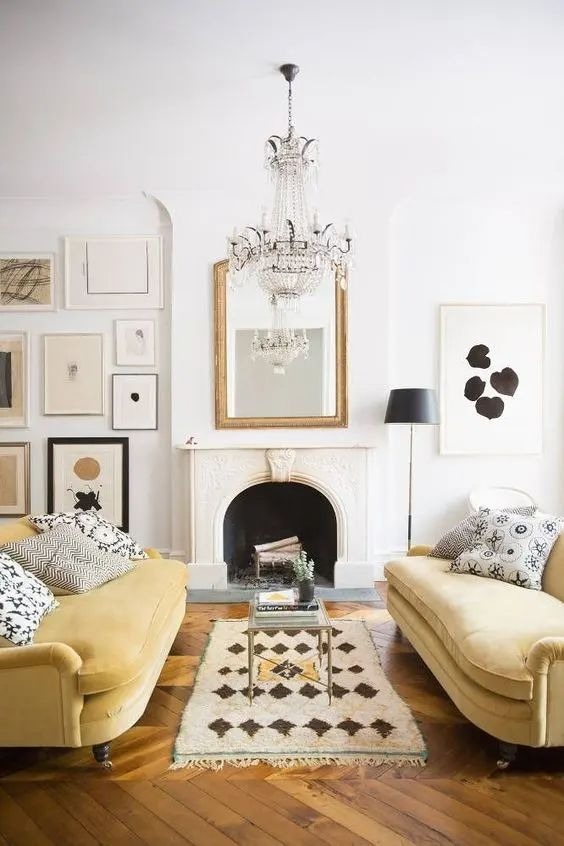 a chic living room with a non working fireplace, a monochromatic gallery wall, a crystal chandelier and a duo of light yellow sofas