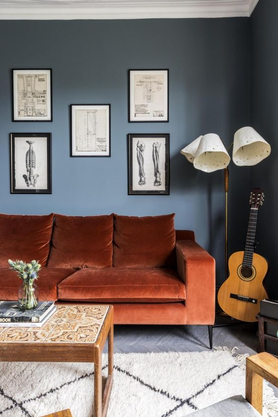 a chic living room with navy walls, a rust-colored sofa, a gallery wall , a floor lamp and low table with tiles is wow