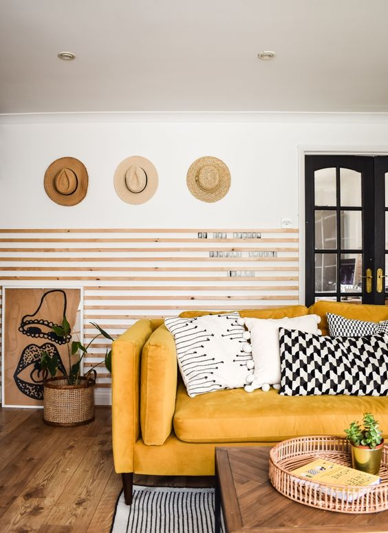 a chic living room with wooden slabs on the wall, a yellow sofa and graphic pillows, hats on display and some plants
