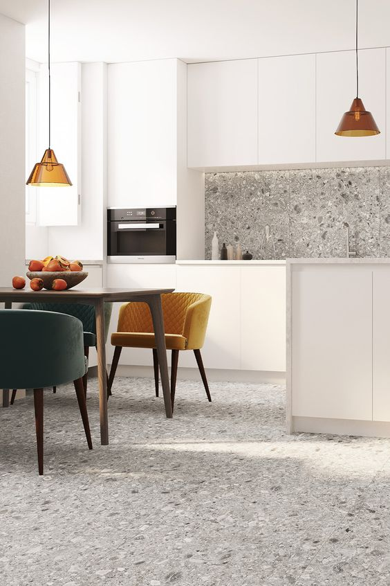 a chic modern kitchen and dining space with grey terrazzo on the floor and backsplash that brings pattern and a bit of color to the space