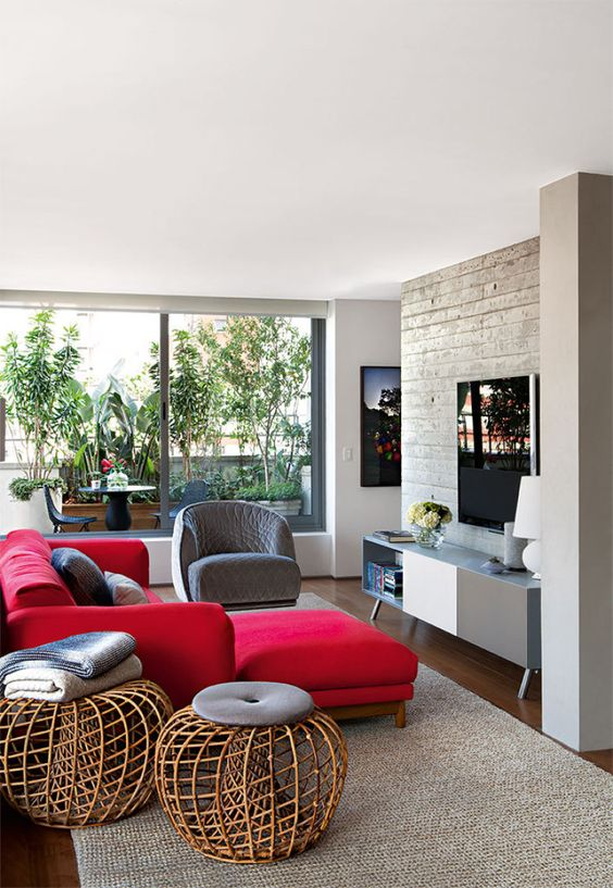 a chic modern living room with a concrete wall, a two tone sideboard, a bold red sectional, a grey chair and rattan ottomans