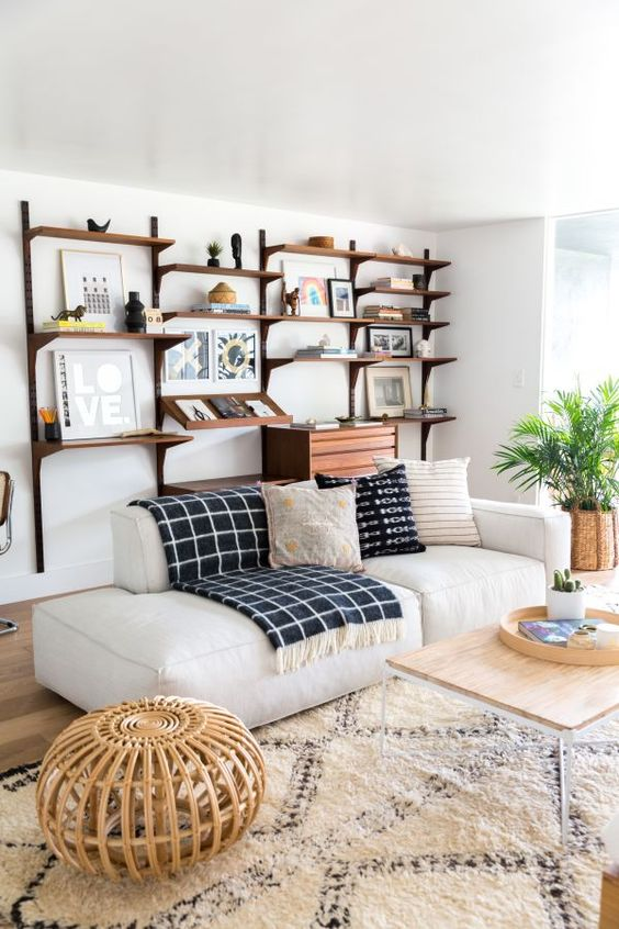 a chic modern living room with a large yet airy storage unit on the wall, a white low sofa, a rattan stool and a table