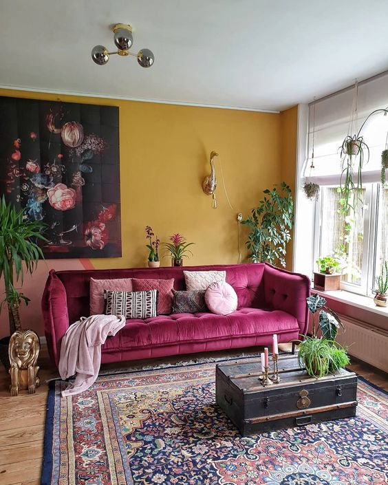 a chic modern living room with a mustard accent wall, a pink sofa, a boho printed rug, a vintage suitcase and potted plants