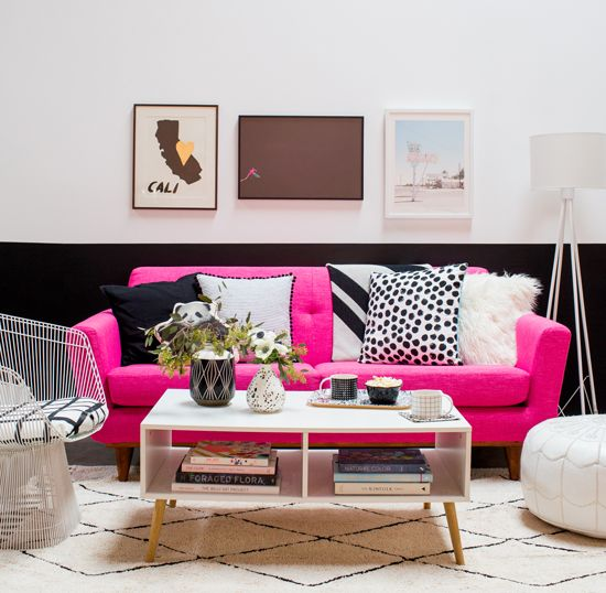 a chic modern lviing room with a color block wall, hot pink sofa, a storage coffee table and a lovely gallery wall