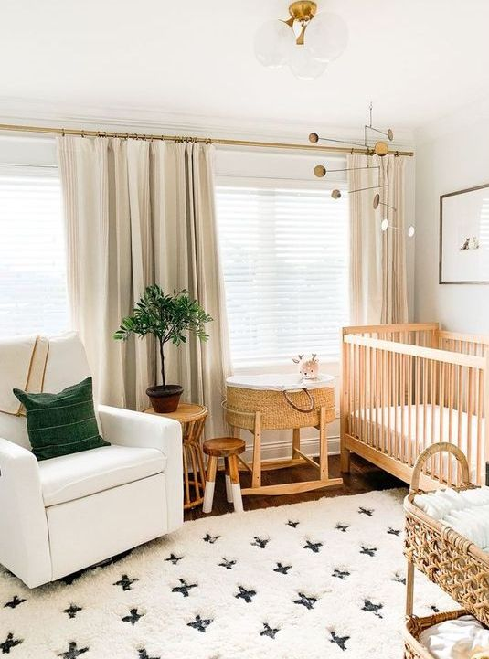 a chic modern nursery with a printed rug, a white chair, a wooden crib and a rattan cart for storage, green touches