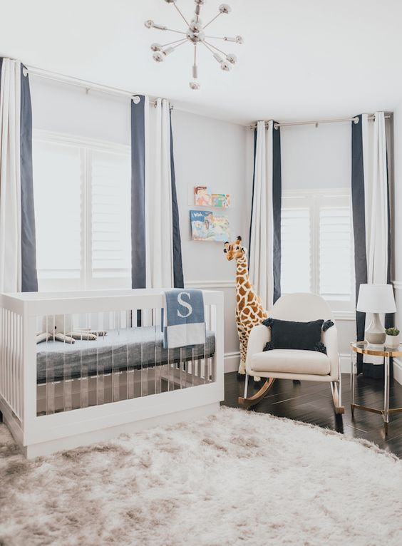 a chic modern nursery with a wood and acrylic crib, a rocker chair, an acrylic table, striped curtains and a dusty pink rug