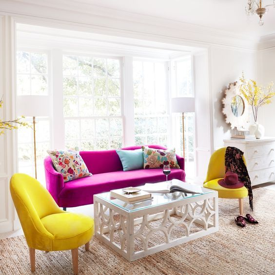 a chic neutral living room in modern farmhouse style, with a hot pink sofa, sunny yellow chairs, a glass table and colorful pillows
