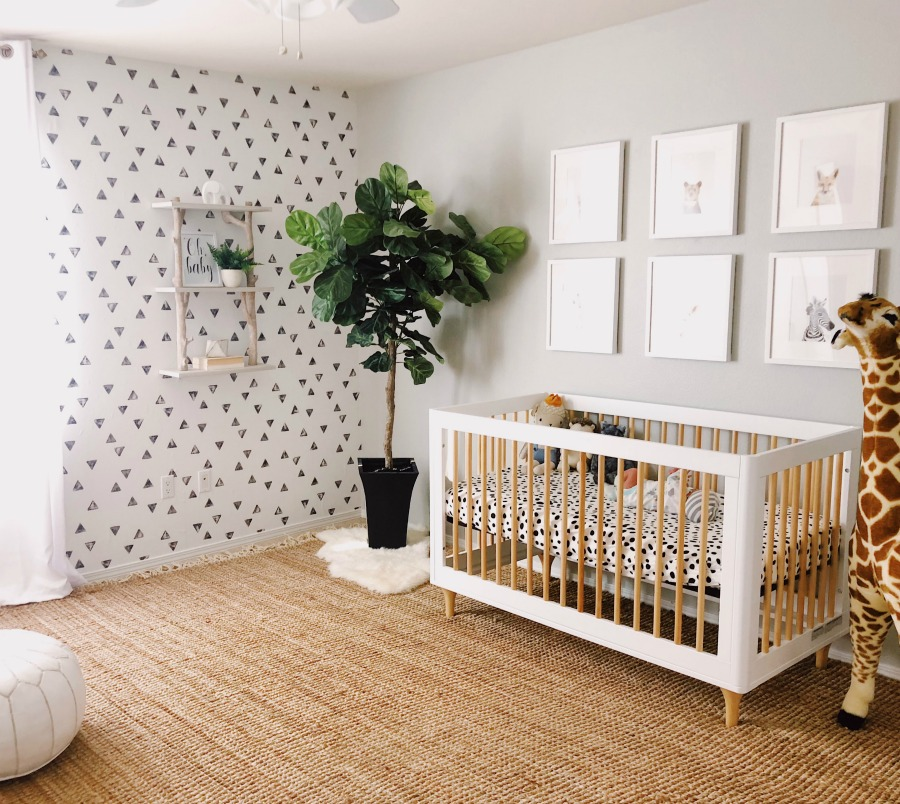 a chic neutral nursery with a geo print wall, a crib with leopard bedding, a chic gallery wall and a potted plant in the corner