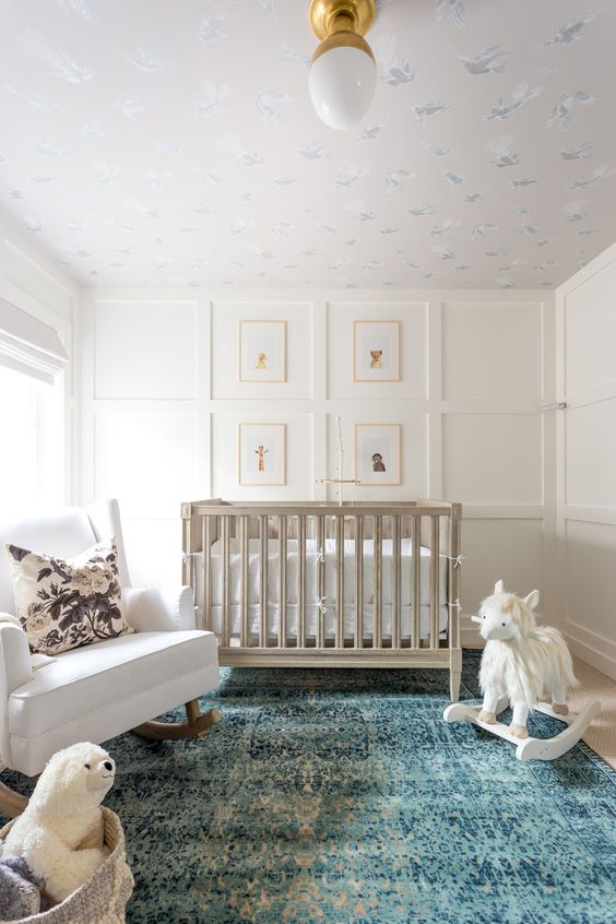 a chic neutral nursery with paneled walls, a grey crib, a white rocker, a basket with toys and a lovely printed ceiling