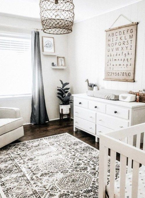 a chic neutral nursery with white furniture, a printed rug, grey curtains, a functional artwork, some shelves with art