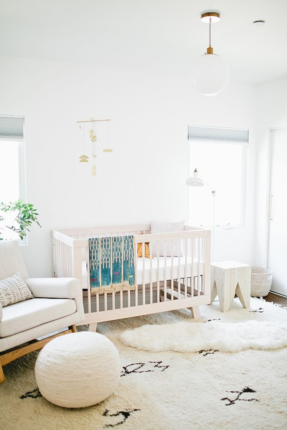 a chic neutral nursery with white furniture, layered rugs, a pouf, a mobile and some lamps is airy and serene