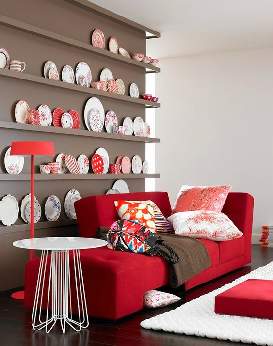 a chic nook with a taupe wall and a collection of decorative plates, a red couch and printed pillows plus a round table