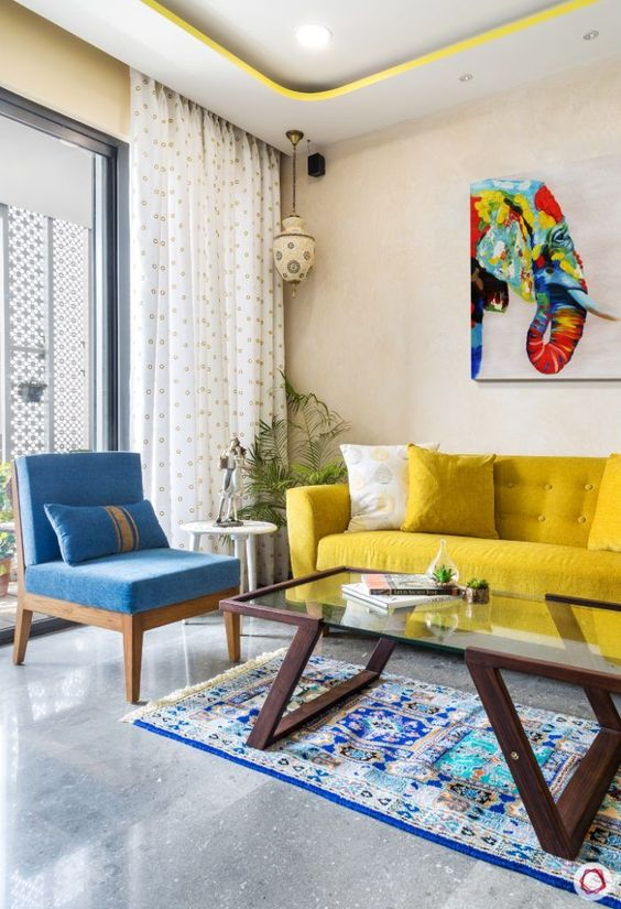 a colorful living room with neutral walls, a yellow sofa, a blue chair, a glass table and a colorful artwork is amazing