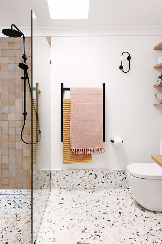 a contemporary bathroom with blush tiles in the shower and a terrazzo floor plus blush textiles and black fixtures