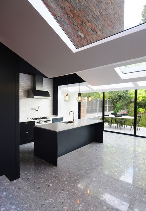a modern kitchen with black cabinets