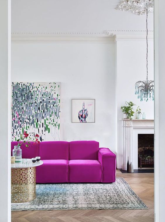 a contemporary living room with a fireplace, a hot pink sofa, cool artworks, a quirky chandelier, a printed rug and a chic table