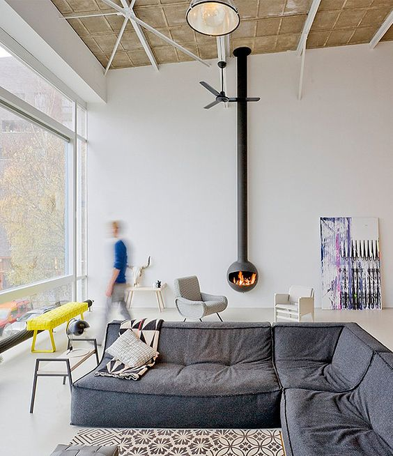 a contemporary living room with a glazed wall, a grey low sofa, a suspended hearth, some pretty furniture is very cool
