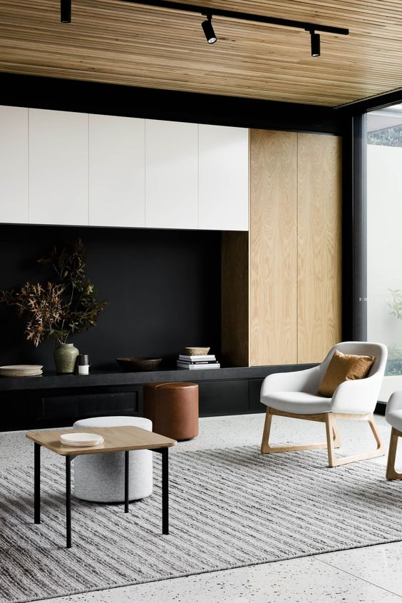 a contemporary living room with a gorgeous storage unit in white, black and blonde wood, with blonde wood furniture and a ceiling