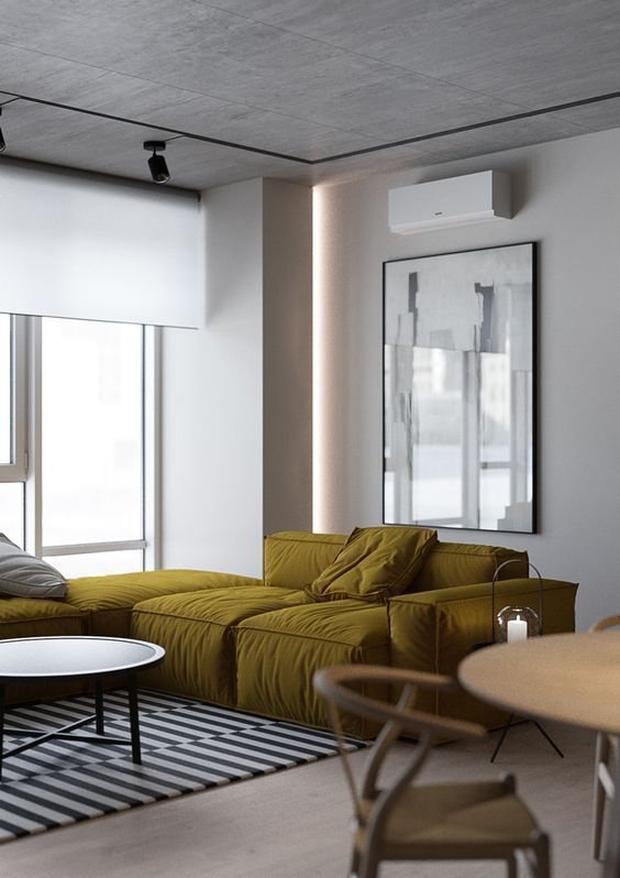 a contemporary living room with a mustard low sofa, a low coffee table, an oversized artwork and a round table and chairs