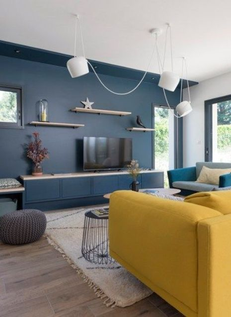 a contemporary living room with a navy accent wall, a yellow sofa, a grey chair, pendant lamps and floating shelves is chic